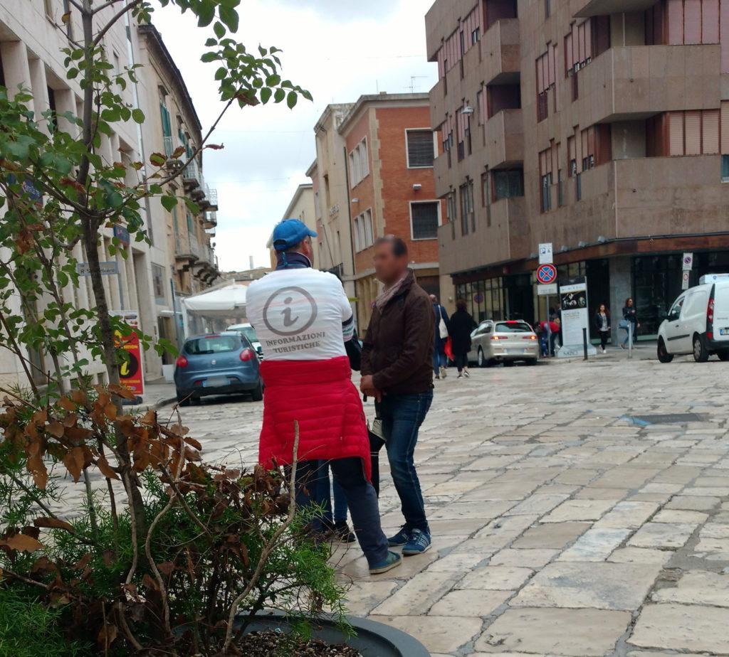 Sei su: Come proteggersi dalle trappole per turisti a Matera. Immagine con falso dipendente comunale che indossa una maglietta con il simbolo delle informazioni turistiche.